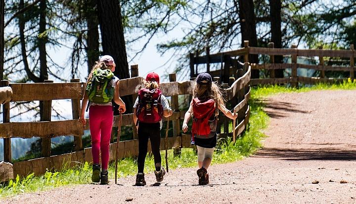 Trzy dziewczynki z plecakami wędrują górską drogą