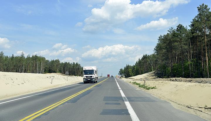Trasa budowanej drogi ekspresowej S17. Biała ciężarówka jedzie po czarny asfalcie. Po bokach lasy. W tle niebieskie niebo z białymi chmurami