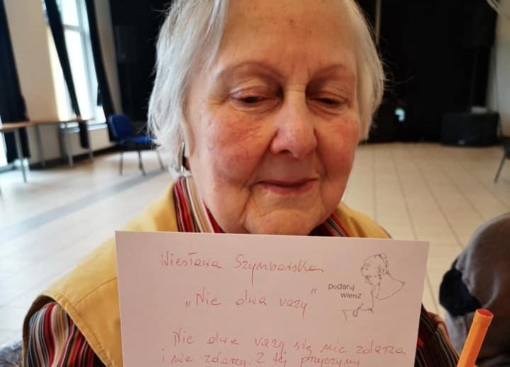 Seniorka prezentuje przepisany przez siebie wiersz Wisławy Szymborskiej