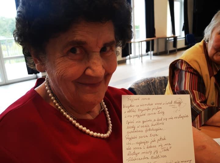 Seniorka prezentuje przepisany przez siebie wiersz