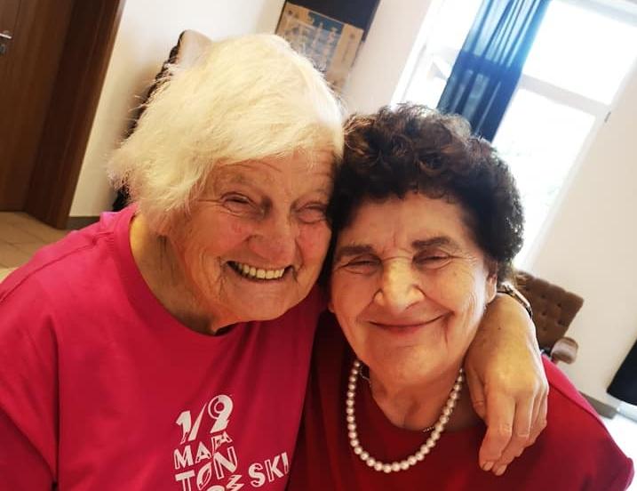 Dwie seniorki przytulają się do siebie i szczerze śmieją się
