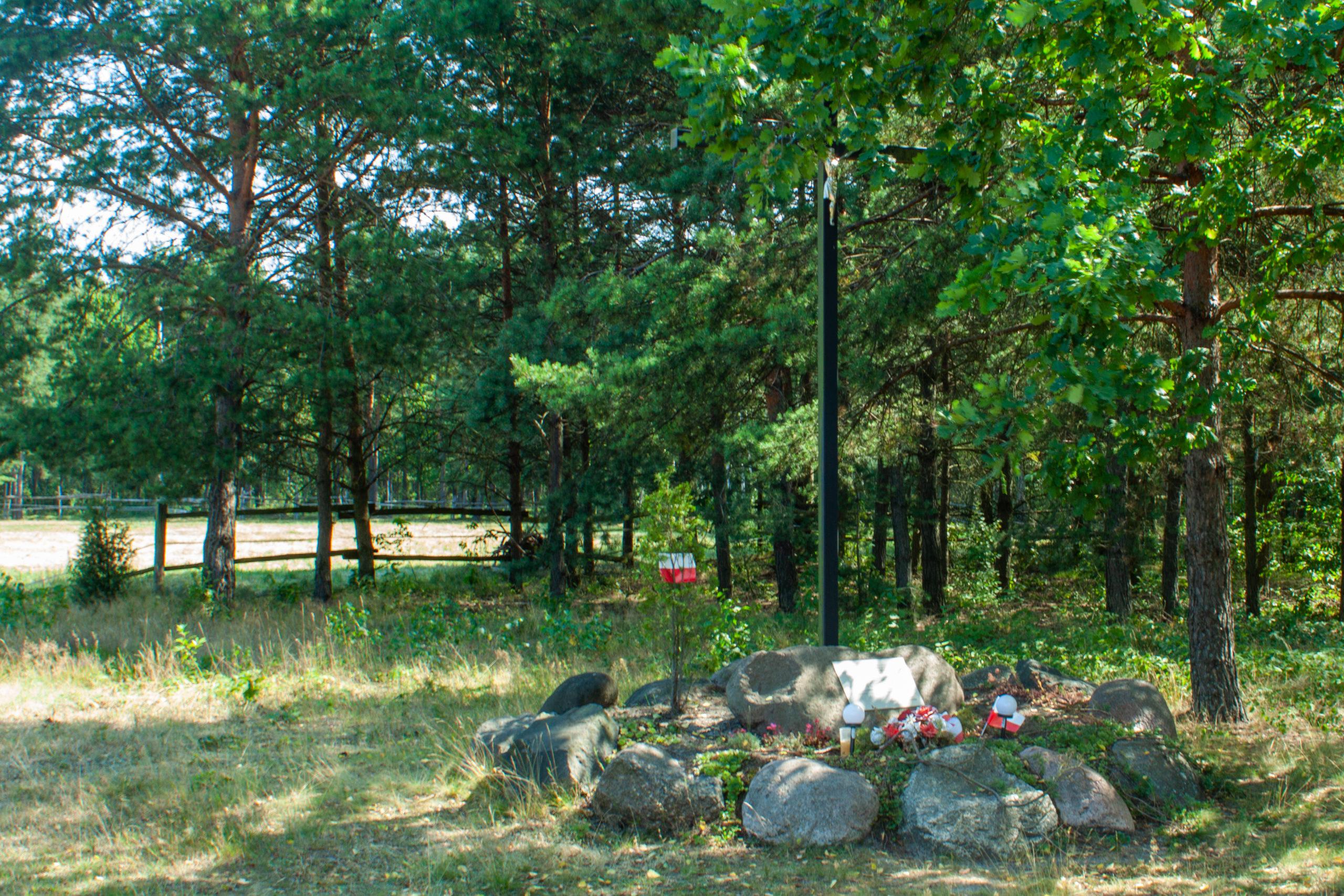 """Zrzutowisko """"Pierzyna"""" w Malcanowie. Czarny, metalowy krzyż, pod nim kopiec kamieni i tabliczka pamiątkowa"""