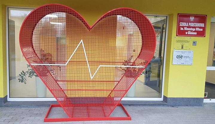 Czerwone, metalowe serce - pojemnik, do którego można wrzucać nakrętki stoi przed Szkołą Podstawową w Gliniance