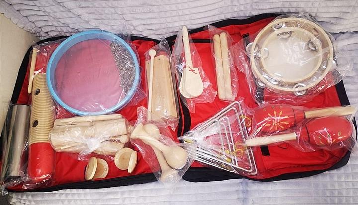 Drewniane instrumenty muzyczne: tamburyn, trójkąty, bębenek, kastaniety, grzechotki i inne ułożone na czerwonym podkładzie