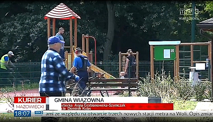 Screen z Kuriera TVP Warszawa. Gminny Park Centrum w Wiązownie. Na pierwszym planie mężczyzna w koszuli w niebiesko-białą kratę. W tle plac zabaw