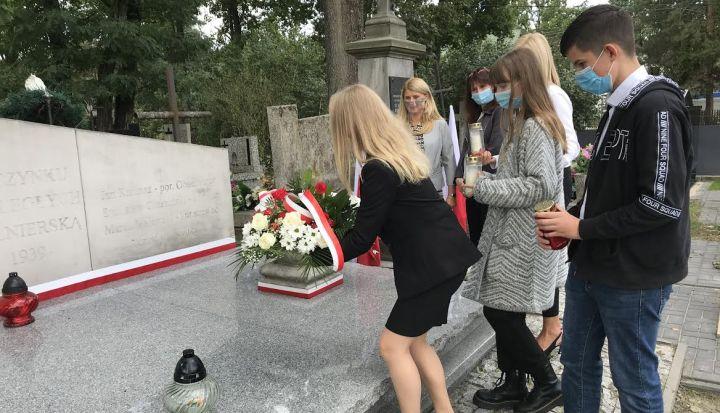 Uczniowie i nauczyciele ze szkoły w Wiązownie składają wiązankę kwiatów na grobie swojego patrona - Bohaterskich Lotników Polskich