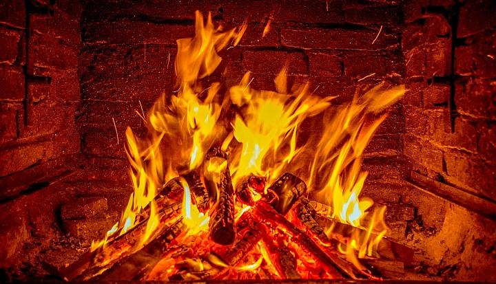 Płonący ogień pomarańczowo-żółto-czerowny wewnątrz kominka