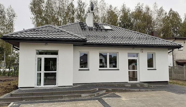 Nowy budynek świetlicy w Rzakcie. Szary dach z dachówki. Białe ściany. Podjazd z kostki szarej, betonowej