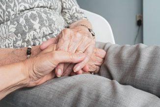 Osoba młodsza trzyma za rękę seniora