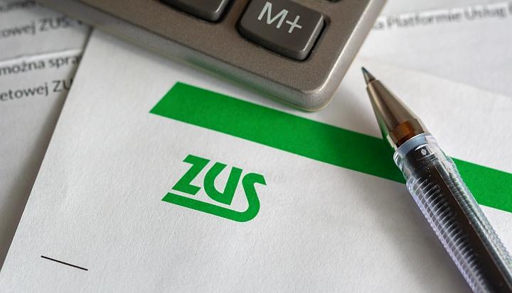 List z zielonym logiem ZUS. Po lewej kalkulatro, po prawej długopis