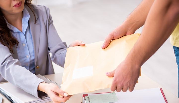 Męskie ręce podają kopertę kobiecie