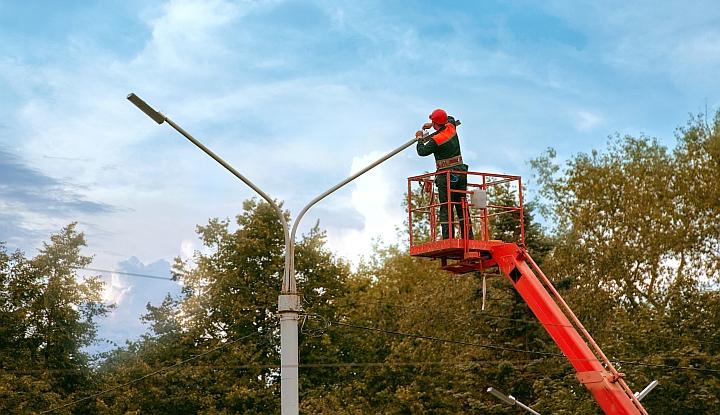 Mężczyzna na czerwony wysięgniku naprawia lampę uliczną