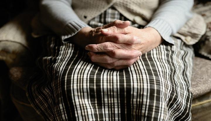 Splecione dłonie starszej kobiety ułożone na kolanach