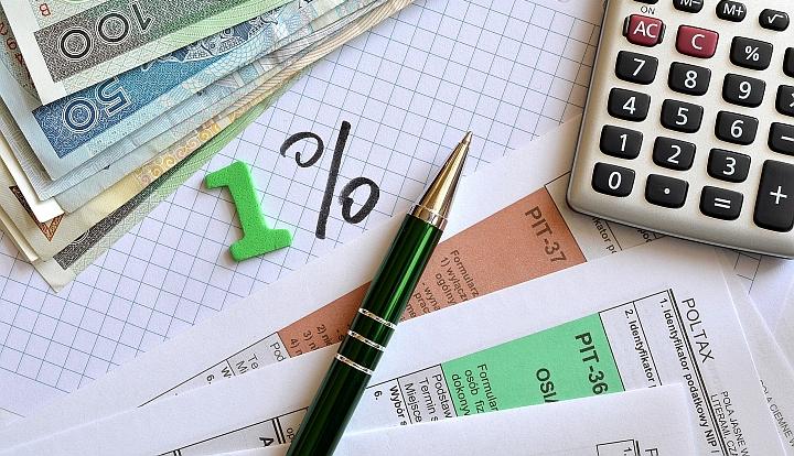 Na kartce w kratkę napis 1 %, wokół ułożone: kalkulator, pity, długopis i banknoty