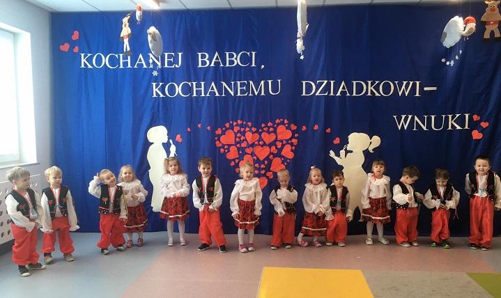 """Dzieci ubrane w krakowskie stroje. Za nimi niebieskie tło, na nim napis """"Kochanej babci, kochanemu dziadkowi - wnuki"""""""