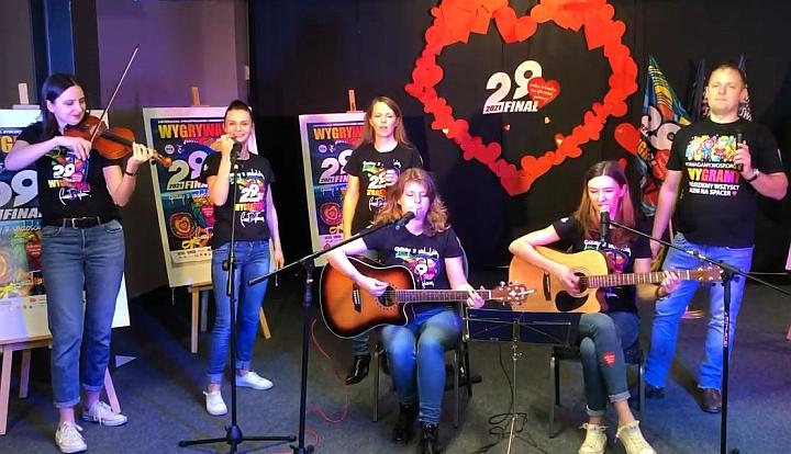 Sześć osób tworzących zespół muzyczy. Grają na skrzypcach i gitarach oraz śpiewają. w Tle plakaty Wielkiej Orkiestry Świątecznej Pomocy