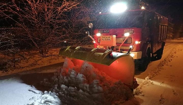 Czerwony wóz strażacki w lesie odśnieża drogę