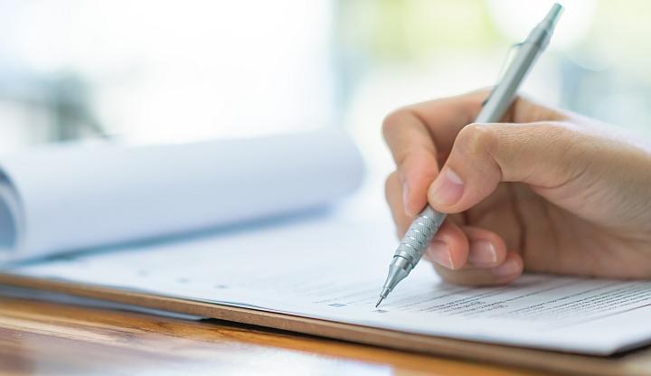 Damska ręka trzyma srebrny długopis. Pisze nim coś na kartce