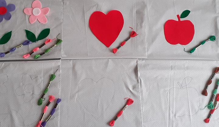 Materiał. Na nim leżą muliny do wyszywania i kawałki przyciętego filcu w kształcei serca i kwiatów