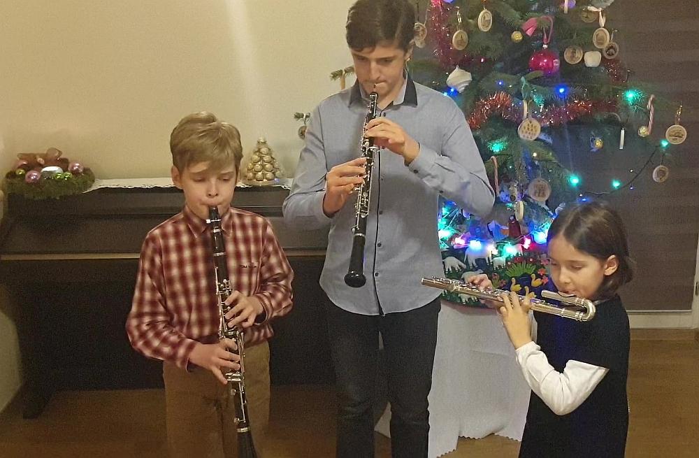 Trójka dzieci. Chłopiec w koszuli w kratę gra na oboju, chłopiec w koszuli niebieskie gra na oboju, dziewczynak w czarnej sukience gra na flecie poprzecznym