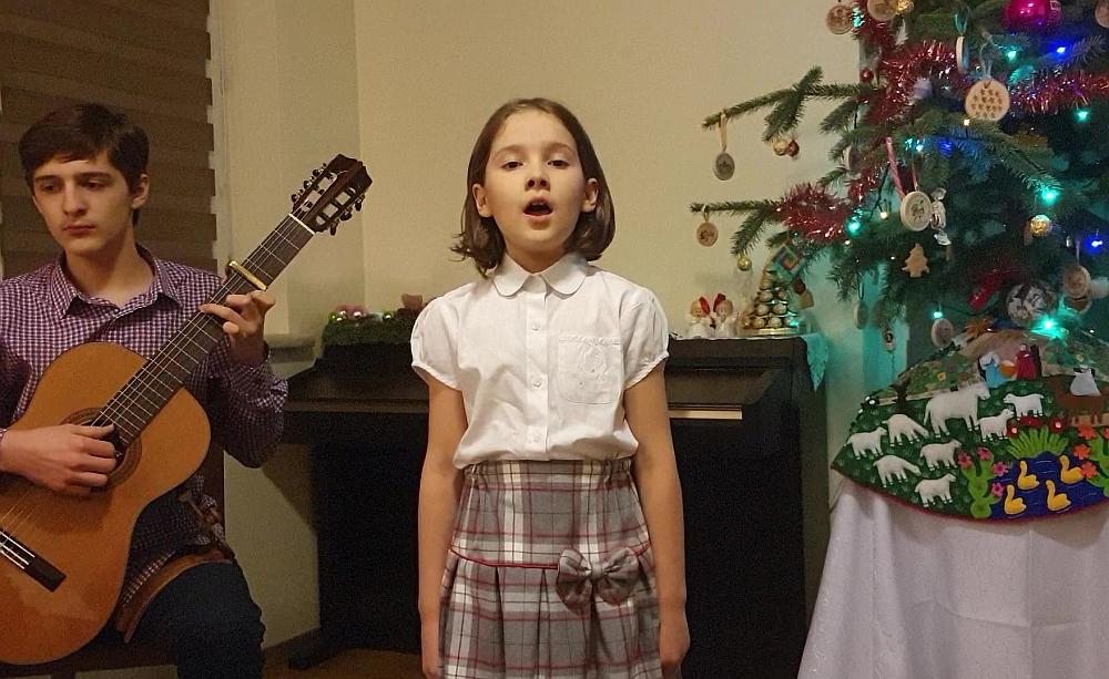Dzeiwczynka w białej bluzce i spudnicy w kratke śpiewa. W tle choinka i chłopiec grajaćy na gitarze