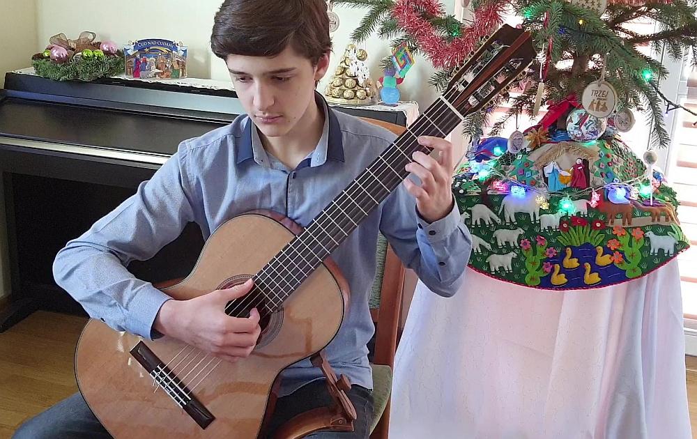 Chłopiec w niebieskiej koszuli gra na gitarze klasycznej