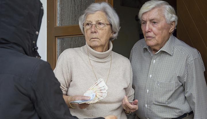 Dwoje starszych ludzi. Kobieta trzyma w ręku pieniądze i przekazuje je mężczyźie w czarnej kurtce, stojącemu tyłem