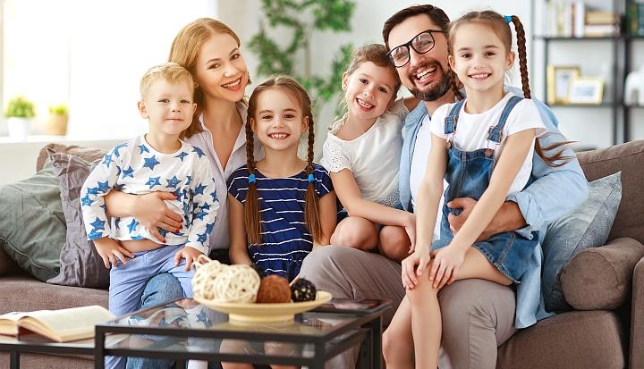Duża rodzina. Kobiet i meżyzna wraz z czwróką dzieci siedzą na brązowej kanapie
