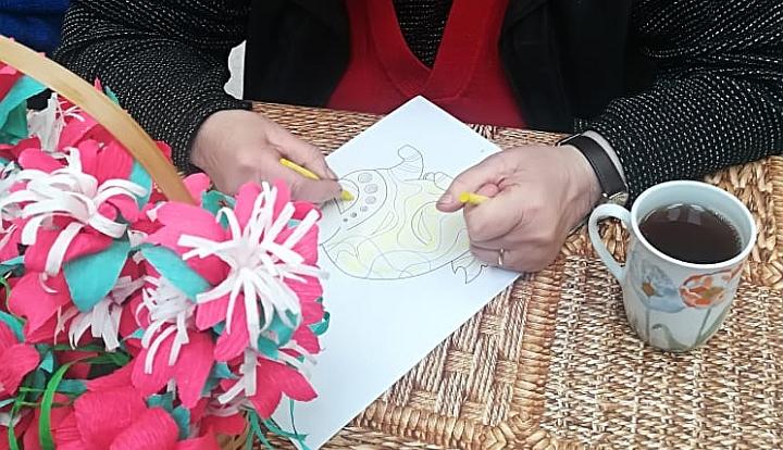 Ręce seniorki, które kolorują obrazek. Z lepwej strony czerowno-białe kwiaty z bibuły, z prawej - kubek z herbatą