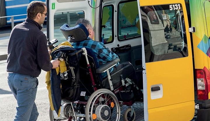 Wężczyzna wtacza wózek inwalidzki z siedzącym na nim mężczyzną po rampie do żółtego samochodu