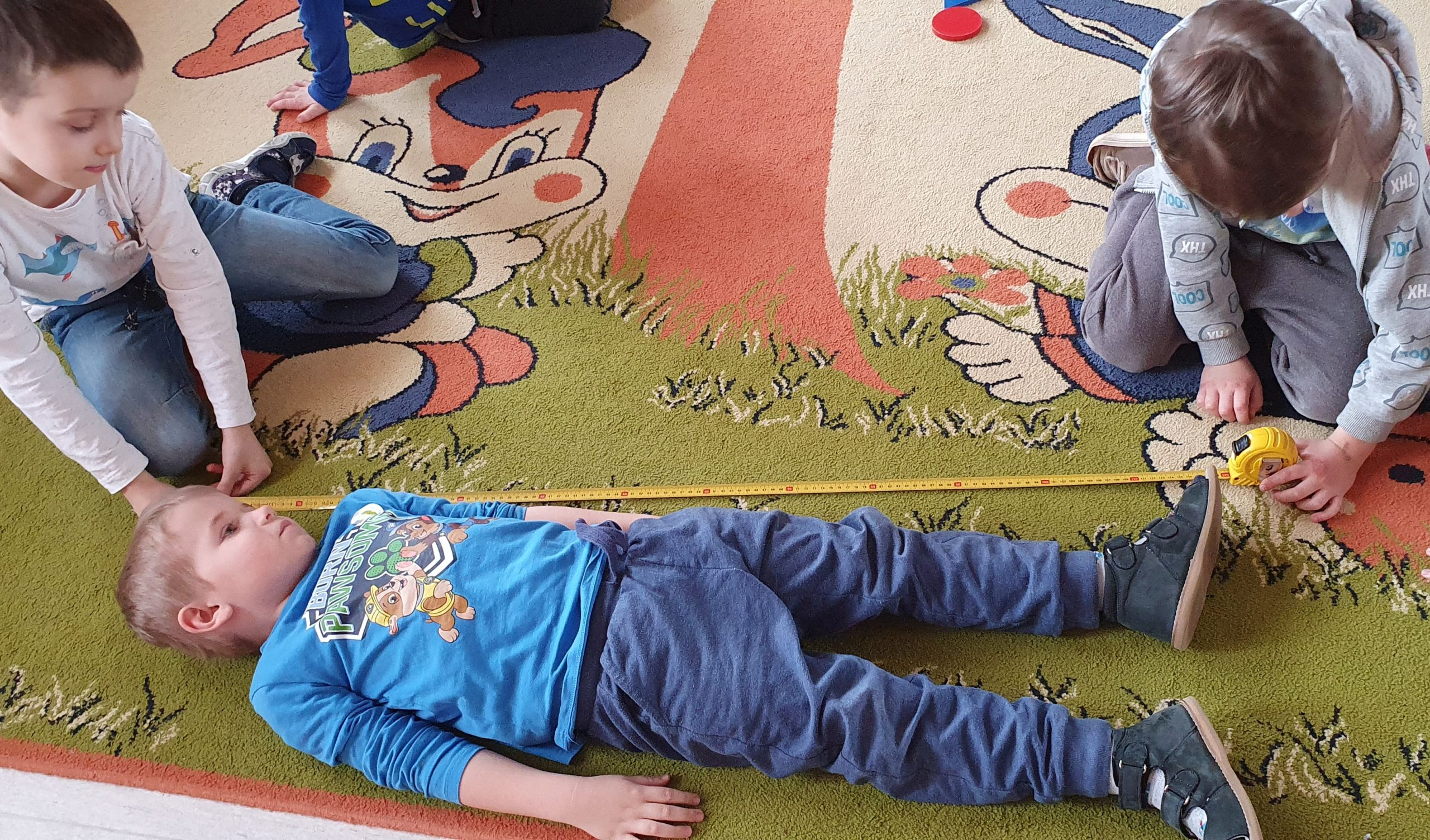 Chłopiec leży na dywanie. Obok dwóch chłopców mierzy jego długość żółtą miarką