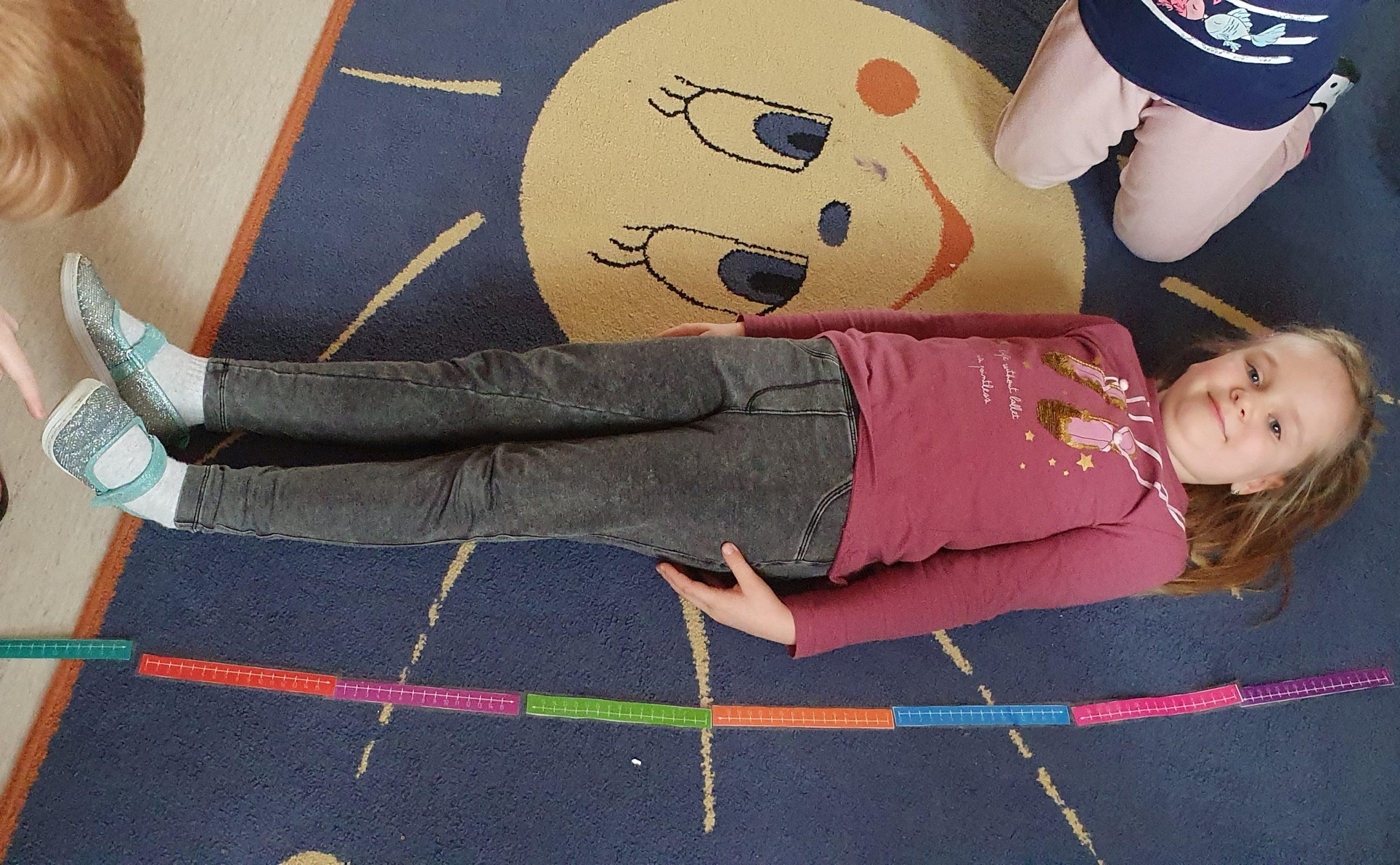 Dziewczynka leży na dywanie. Obok kolorwe miarki