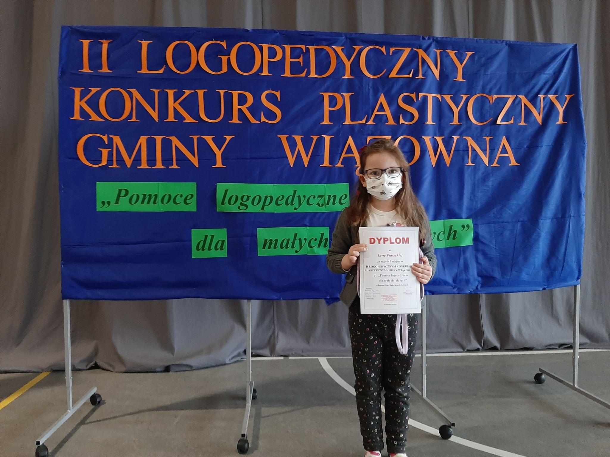 Tablica z napisem II Konkurs Logopedyczno-Plastyczny Gminy Wiązowna. Dziewczynka z dyplomem