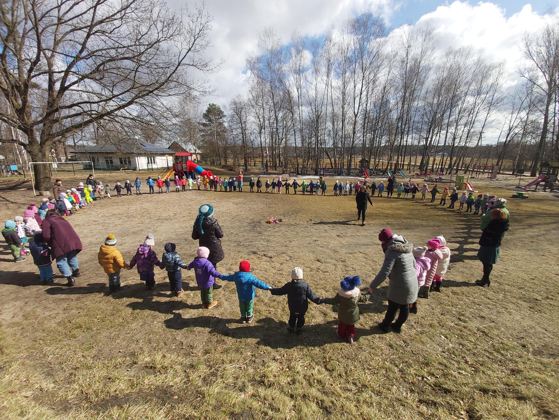 Dzieci na przedszkolnym placu zabaw stoją w kręgu i trzymają się za ręce