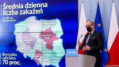 Minister Niedzielski na konferencji prasowej. W tle mapa Polski z naniesionymi rejonami i danymi co do zakażeń koronawirusem