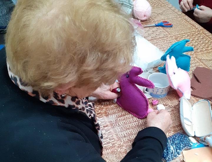 Kobieta szyje fioletowe króliczka z filcu