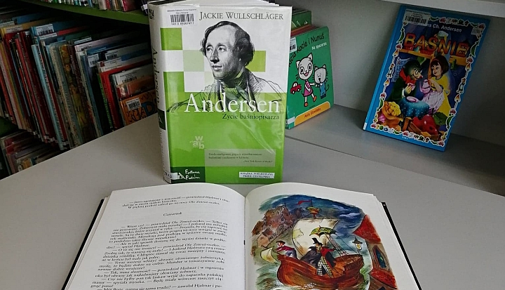 Książka z biografią Andersena oraz rozłożona książka przed nią. Widać tekst i ilustrację