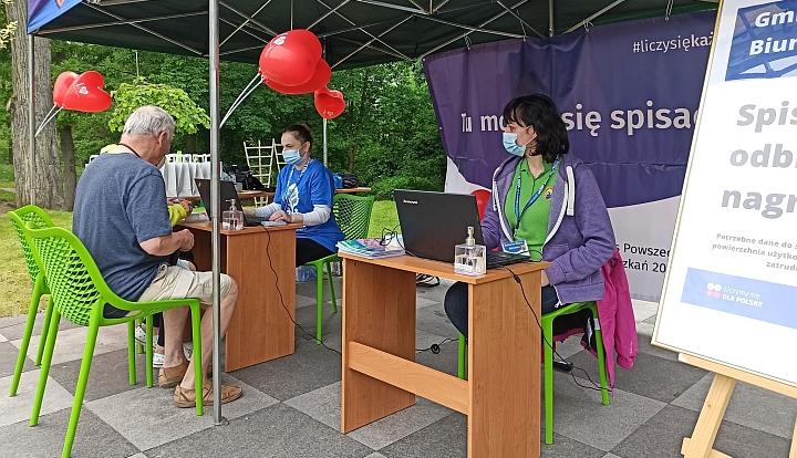 Gminne Stoisko Spisowe. Na zielonym krześle siedzi mężczyzna. Przed nim kobieta w niebieskiej koszulce pisze cos na komputerze