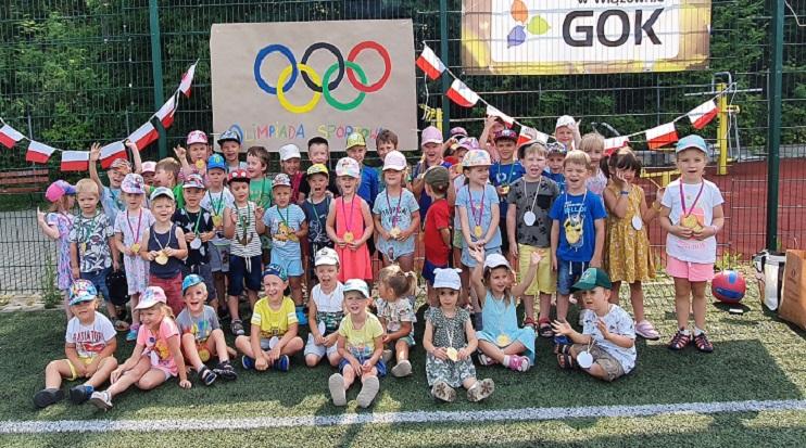 Grupa dzieci w wieku przedszkolnym. W tle tablica z symbolem olimpiady i napisem GOK.