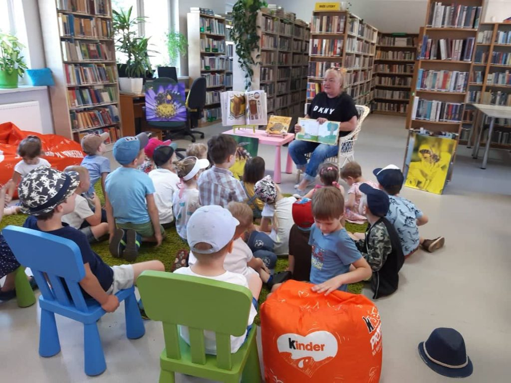 Pani czytająca grupie dzieci książkę
