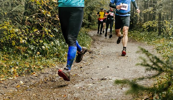 Ścieżka leśna. Po nij biegną sportowy. Widać nogi i zabłocone buty