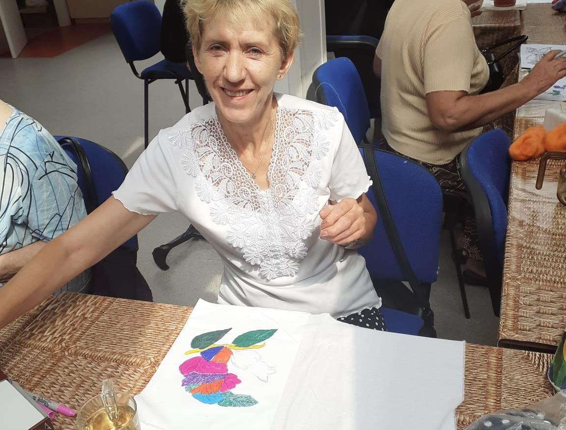 Seniorka maluje kwiaty na tkaninie