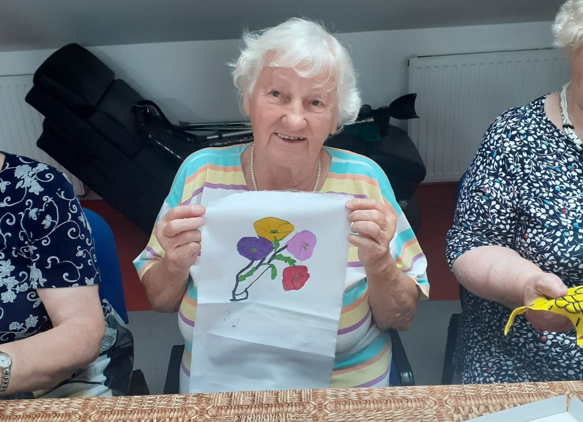 Seniorka trzymająca w ręku tkaninę z namalowanymi na niej kolorowymi kwiatami