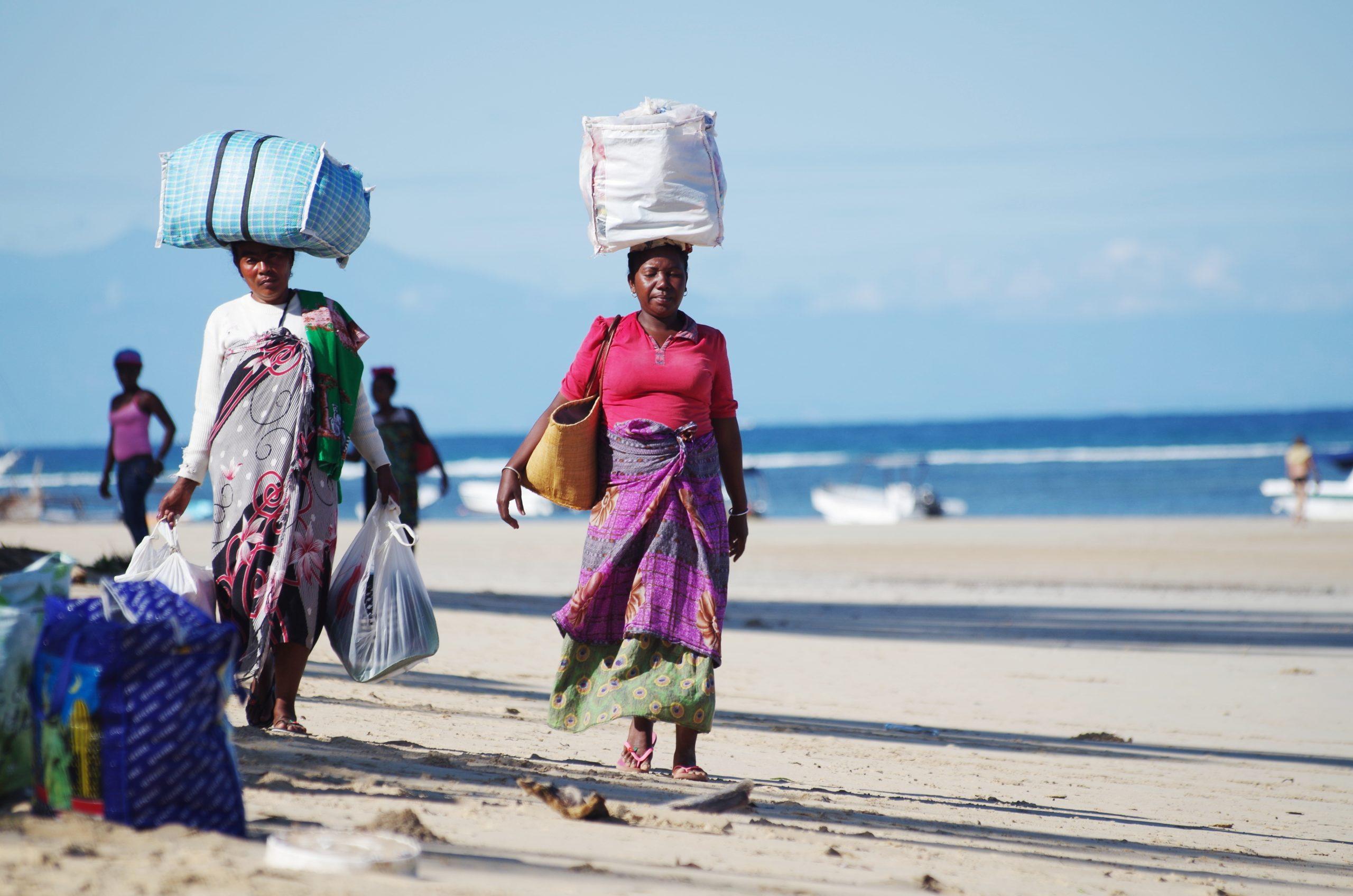 Kobiety z Madagazkaru w kolorowych ubraniach niosą na głowach paczki