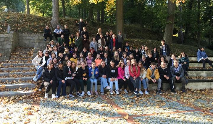 Duża grupa młodych ludzi siedzi na kamiennych schodach w parku