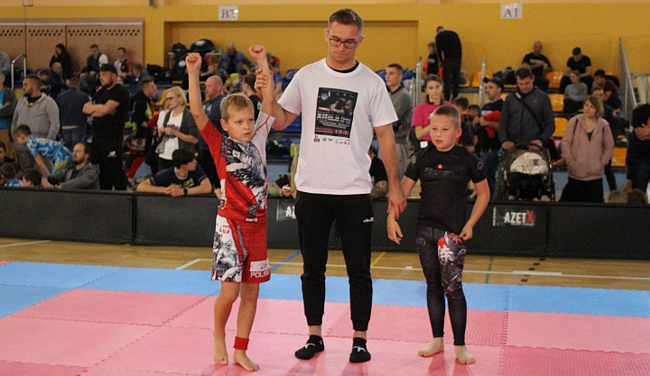 Zawody jiu jitsu. Sędzia podnosi do góry rękę chłopca w biało-czerwono-czarnym stroju. PO prawej stoi zasmucony chłopiec ubrany w czarną koszulkę i spodenki.