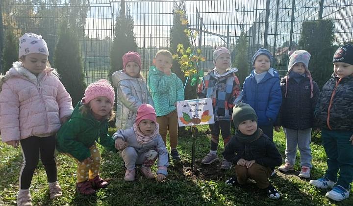 Grupa małych dzieci pozuje do wspólnego zdjęcia przy posadzonym przez siebie małym drzewku